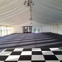 Internals of a marquee with substructure flooring, carpet, linings, chandeliers and dancefloor
